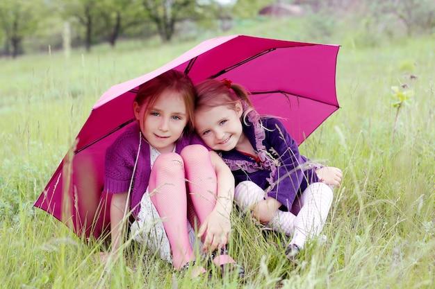 Kleine meisjes zusters bedekken onder paraplu