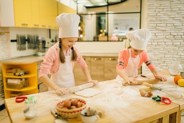 Kleine meisjeschefs met deegrollen, grappige bakkers