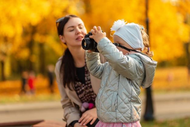 Kleine meisjesfotograaf met een camera maakt een foto in het herfstgele park. dochter met moeder in de natuur