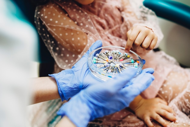 Kleine meisjeshand die zijn gevoel voor haar tanden in een pediatrische stomatologie kiezen.