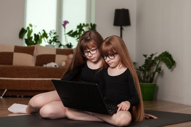 Kleine meisjeszusjes houden thuis een online les turnen