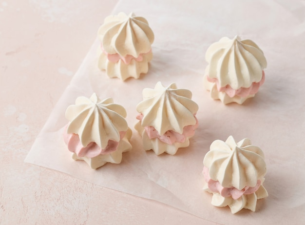 Kleine meringuecakes gemaakt van eiwitkoekjes en aardbeienroom op roze achtergrond