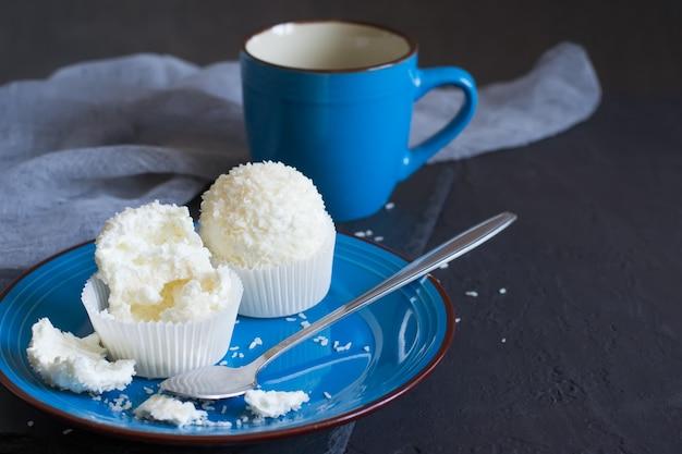Kleine meringuecakes pavlova met glazuur en kokosnoot op een blauw bord. selectieve focus met kopieerruimte