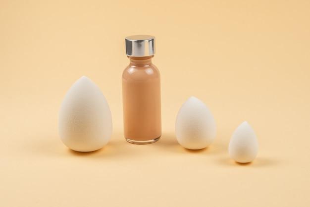 Kleine, middelgrote en grote witte schoonheidsmixer en make-upstichting op beige achtergrond.