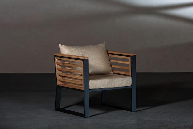 Kleine moderne stoel met een beige kussen erop in een kamer