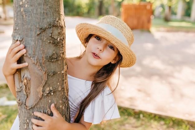 Kleine modieuze dame verstopt achter boom, tijdens het spelen in park in zomerdag. vrij donkerbruin meisje in hoed met wit lint en elegante kleding vakantie buiten doorbrengen.