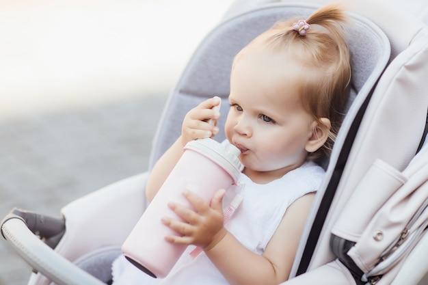 Kleine mooie baby die in een kinderwagen zit en water of melk drinkt uit haar thermoskan