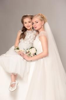 Kleine mooie meisjes met bloemen gekleed in trouwjurken