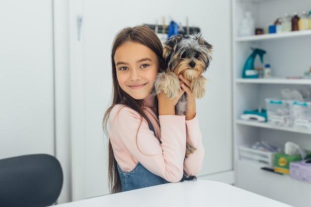 Kleine, mooie meisjeseigenaar met haar schattige yorkshire terrier in de veterinaire kliniek.