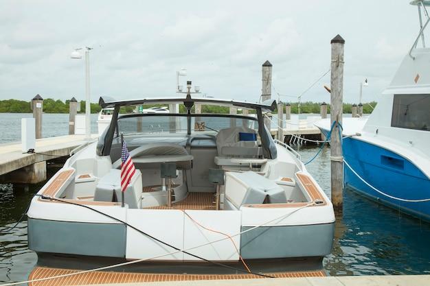 Kleine motorboot die bij de jachthaven in zonsondergangtijd aanmeert