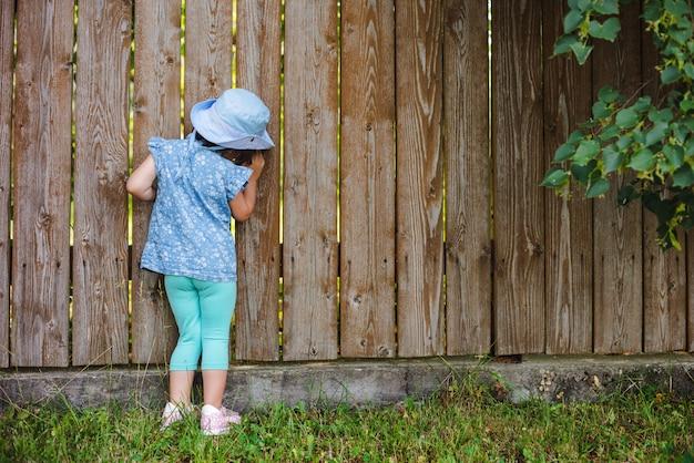 Kleine nieuwsgierige jongen schittert uit het gat in het hek in de wereld buiten zijn achtertuin.