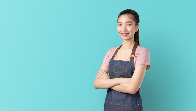 Kleine onderneming, aziatische vrouw in schort en status met gekruiste wapens tegen en vooruit kijkend.