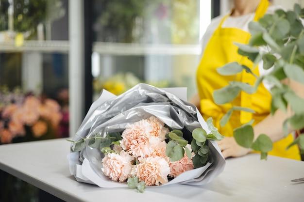 Kleine onderneming. bloemist ongericht in bloemenwinkel. floral design studio, boeket maken. bloemen bezorgen, zijaanzicht van de bestelling maken