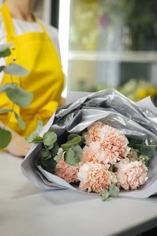 Kleine onderneming. bloemist ongericht met roze bloemen in bloemenwinkel. floral design studio, boeket maken. bloemen bezorgen, verticale bestelling creëren