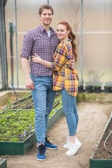 Kleine onderneming. gelukkige jonge lange man en vrouw met lang rood haar die elkaar overdag knuffelen in hun kas