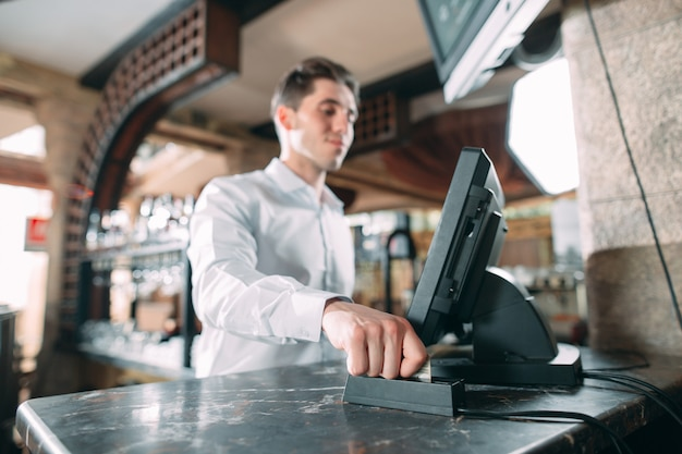 Kleine onderneming, mensen en de dienst - gelukkige mens of kelner in schort bij teller met kassa die bij bar of koffiewinkel werken.