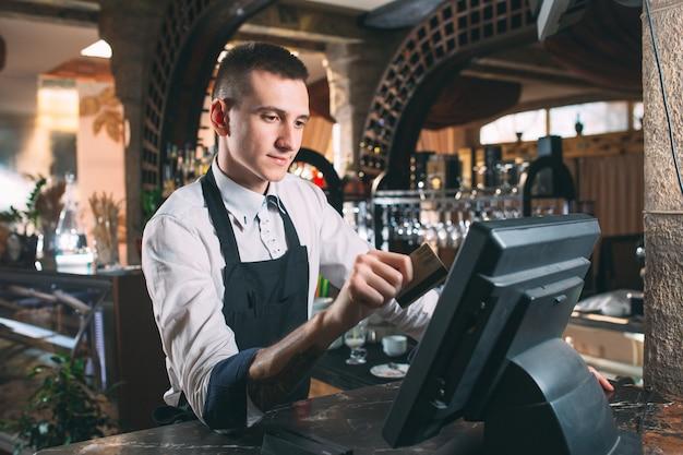Kleine onderneming, mensen en de dienstconcept - gelukkige mens of kelner in schort bij teller met kassa werken bij bar of koffiewinkel
