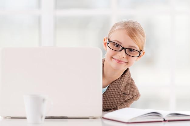 Kleine onderneming. schattig klein meisje met een bril en formalwear kijkt uit de laptop en glimlacht terwijl ze aan tafel zit