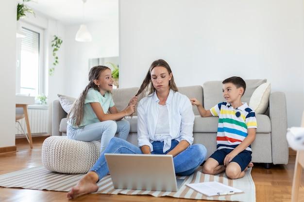 Kleine ondeugende kinderen die moeder freelancer lawaai maken en afleiden die zich op laptop probeert te concentreren en hoofd samenknijpt aan tafel in lichte woonkamer