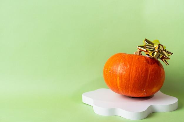 Kleine oranje pompoen op groene achtergrond met kopie ruimte. concept viering van halloween of thanksgiving. cosmetica podium voor halloween. herfst stilleven.