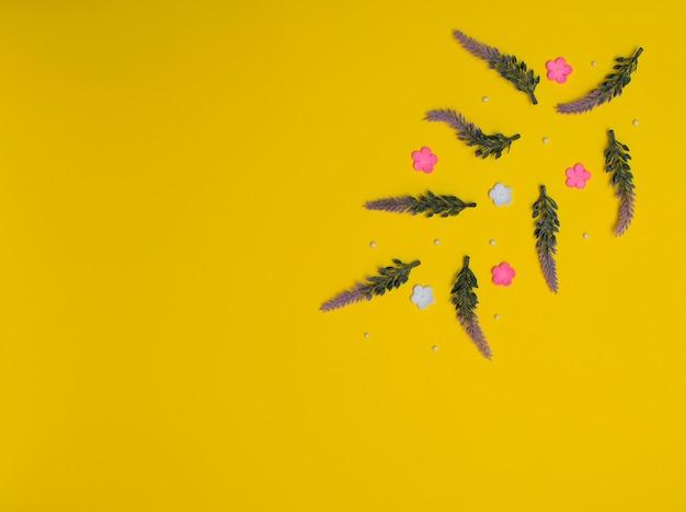 Kleine paarse roze en witte bloemen met witte kralen op gele achtergrond lente zomer concept plat