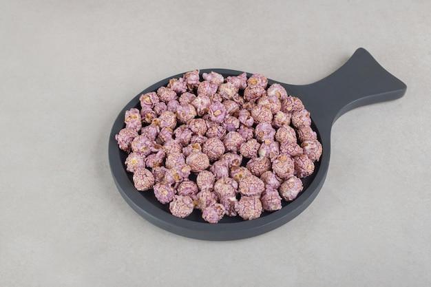 Kleine pan met paars gekleurde popcorn op marmeren ondergrond.