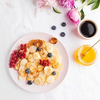 Kleine pannenkoeken met bessen, honing en bloemen op een wit tafellaken en ruimte voor tekst