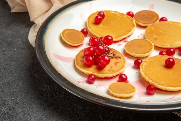 Kleine pannenkoeken met rode bessen op donker
