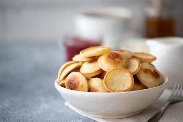 Kleine pannenkoekjes met bessen, jam en poedersuiker