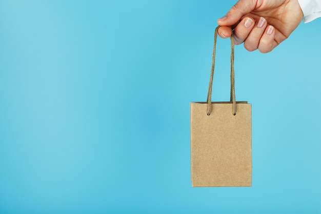 Kleine papieren zak op arm's lengte, bruine ambachtelijke tas voor afhaalmaaltijden geïsoleerd op blauwe achtergrond. sjabloonlay-out van de verpakking met ruimte voor kopiëren, reclame.