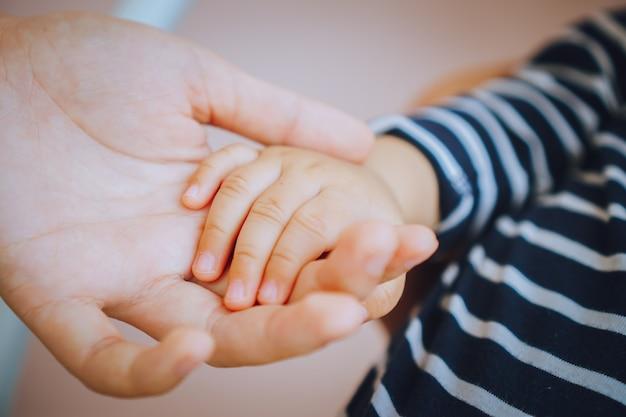 Kleine pasgeboren baby's voeten op vrouwelijke hartvormige handen gelukkig familieconcept
