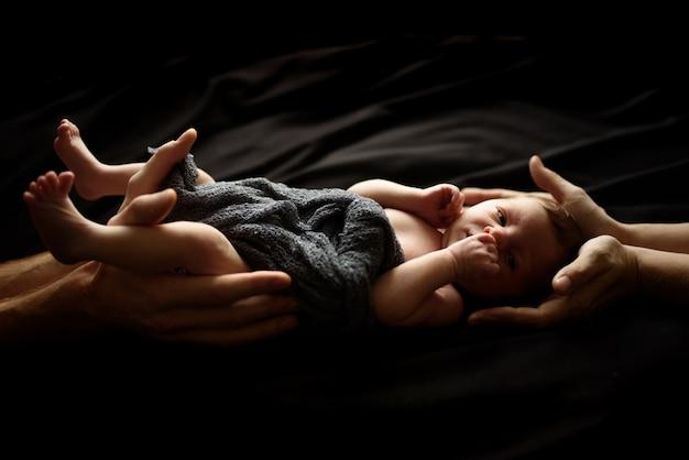 Kleine pasgeboren jongen op zwart. boven- en onderkant van de jongen ondersteunen de handen van ouders.
