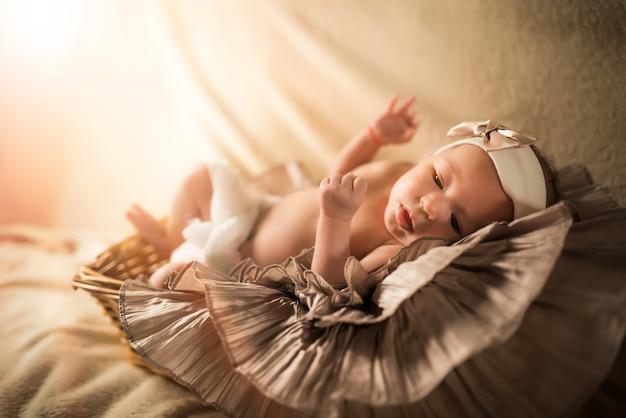 Kleine pasgeborene met een verband om het hoofd ligt met open mond, zijn armen en benen buigend.