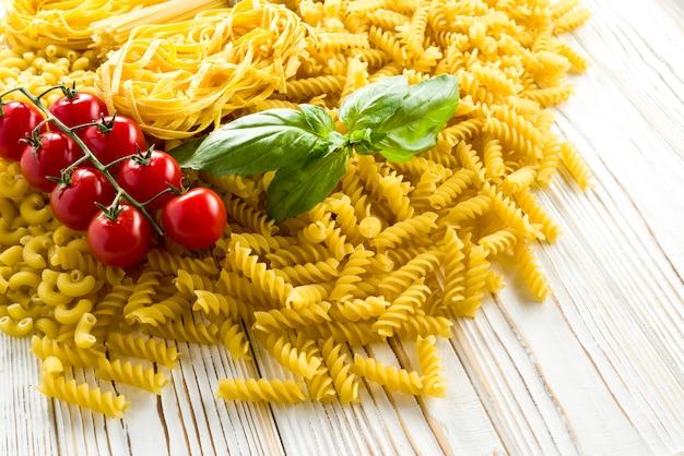 Kleine pasta voor soepen, gekrulde pasta en basilicum blad met tomaten op tafel