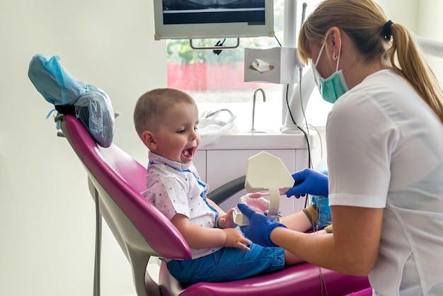 Kleine patiënt die kijkt hoe hij de tanden goed moet poetsen