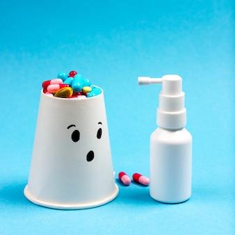 Kleine patiënt met pillen en een fles keelspray op een blauwe achtergrond behandeling van verkoudheid