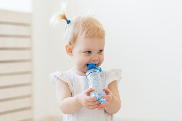 Kleine peuter babymeisje met fles water thuis