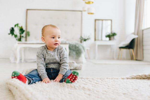 Kleine peuter jongen zittend op een grote deken op de vloer