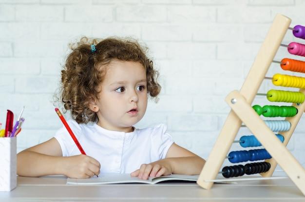 Kleine peuter meisje wiskunde leren. kind rekent op de rekeningen. ontwikkeling, opvoeding, onderwijs en opleiding van kinderen.
