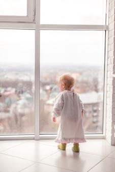 Kleine peuter met blond haar die naar het grote raam kijkt