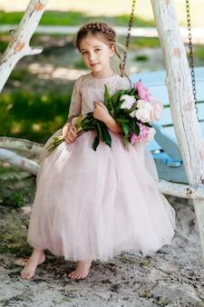 Kleine peuter mooi meisje met bloemen in roze jurk op prachtige tuin