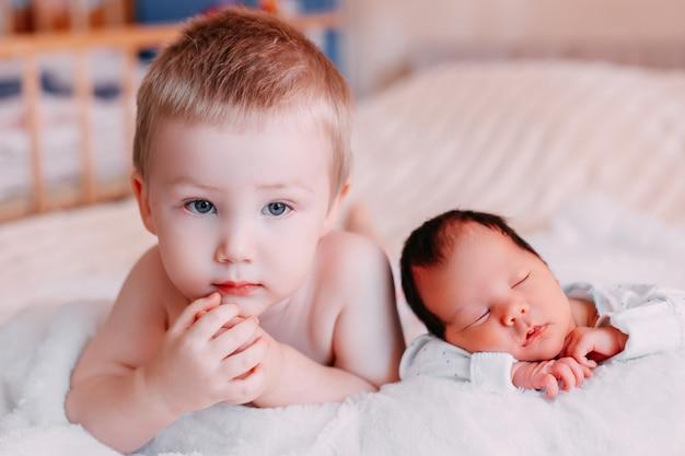 Kleine peuterbroer die dichtbij pasgeboren babyzuster ligt, hij is niet zo gelukkig wegens het