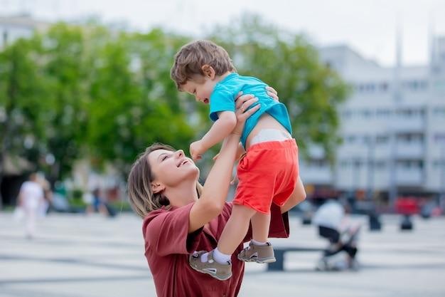 Kleine peuterjongen en moeder hebben plezier op straat in de stad