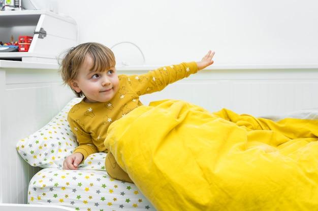 Kleine peuterjongen ligt in bed. kind wordt 's ochtends wakker.