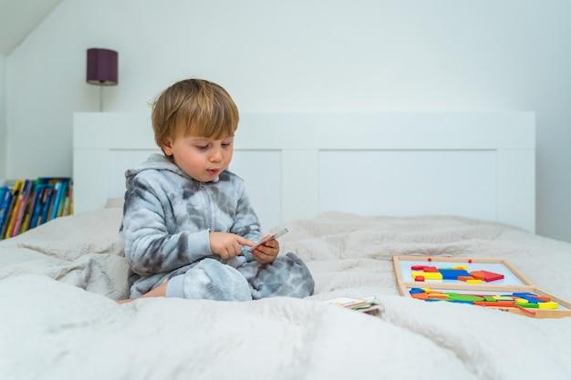 Kleine peuterjongen speelt op het bed in een houten magnetische constructeur