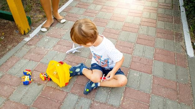Kleine peuterjongen zittend op de grond in het park en spelen met speelgoedauto's