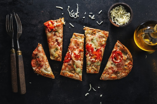 Kleine pizzastukken met kaas op donkere achtergrond. uitzicht van boven.