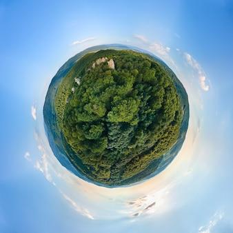 Kleine planeetbol met donkere bergheuvels bedekt met groene gemengde dennen en weelderige bossen omringd met heldere blauwe lucht met witte wolken.