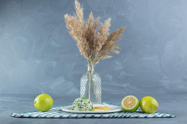 Kleine portie gekookte rijst met citroenen op een opgevouwen tafelkleed, naast een decoratieve bundel veergrasstengels op een marmeren achtergrond.