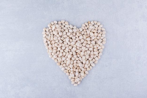 Kleine portie kikkererwten gerangschikt in een hartvorm op marmeren oppervlak